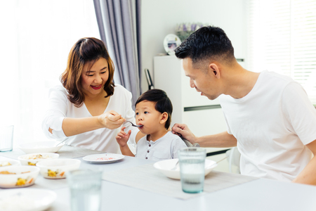 Asian parents feeding their child and the whole family having meal together at home Standard-Bild
