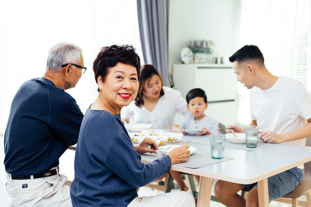 Happy Asian extended family having dinner at home full of happiness and smiles