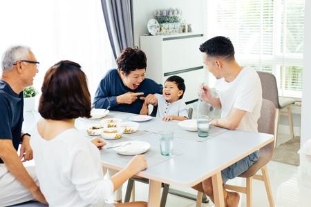 Familia extendida asiática feliz cenando en casa llena de risas y felicidad