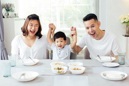 Happy Asian family raising child's hands up and smiling while having a meal together