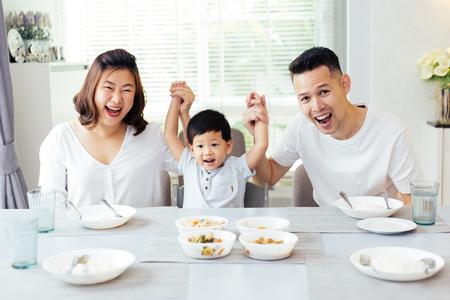 Gelukkige Aziatische familie die de handen van het kind opheft en glimlacht terwijl het hebben van een maaltijd samen Stockfoto