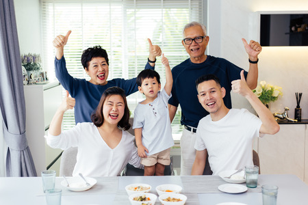 Extended Asian family of three generations having a meal together and showing thumbs up at home with happiness