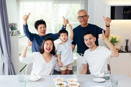 familia asiática de tres generaciones que tienen una comida juntos y mostrando sus pulgares para arriba en casa con felicidad Foto de archivo