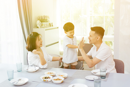 Happy Asian family is giving high five with each other while having dinner at home Foto de archivo