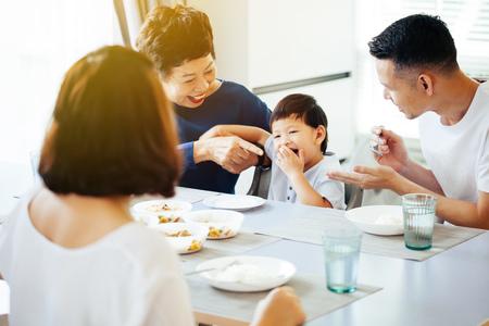Glückliche asiatische Großfamilie, die zu Hause voller Lachen und Glück zu Abend isst
