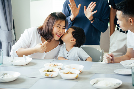 Boy kissing mother on cheeks with the whole Asian family of three generations together at home