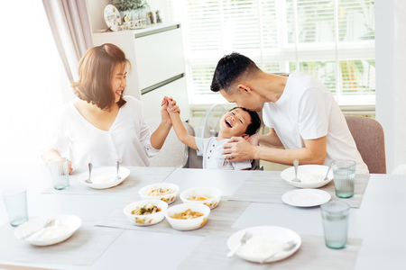 Happy Asian family of father, mother and son playing and laughing while having dinner