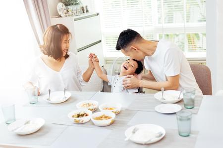 Gelukkige Aziatische familie van vader, moeder en zoon die en terwijl het eten spelen lachen Stockfoto