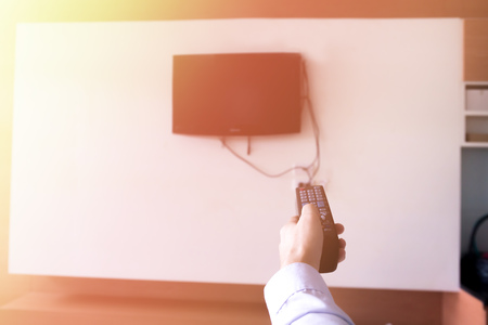Human hand holding a remote controller to turn on and off the television