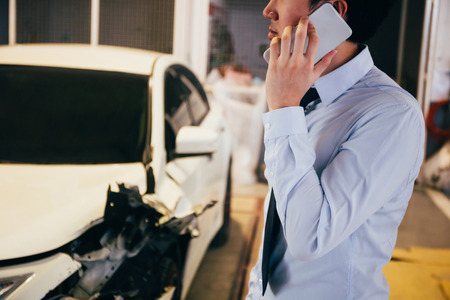 Stressful and upset young man in office business suit giving a call and talking on the phone for wrecked car crash