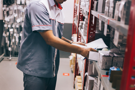 Male inventory worker on duty checking and inspecting stocks in warehouse or storehouse in control