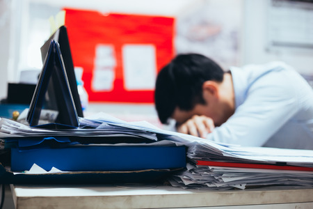 Stressful and frustrated young Asian business office worker having overwork problem crisis with tons of paperwork load Stockfoto - 100021500