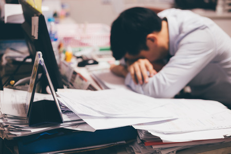 Stressful and frustrated young Asian business office worker having overwork problem crisis with tons of paperwork load