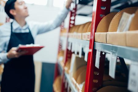 Agent d'inventaire masculin en service de vérification et d'inspection des stocks dans l'entrepôt ou l'entrepôt sous contrôle - (mise au point sélective à l'avant) Banque d'images - 100021503