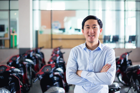 Young Asian man in business office outfit posing in front of many motorcycles in the company office in the background
