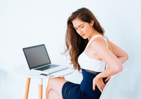 Young Caucasian working business woman on desk with laptop suffering lower back and hip pain as result from office syndrome