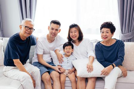 Famiglia allargata asiatica felice che si siede sul divano insieme, in posa per le foto di gruppo