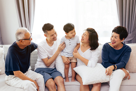 Happy Asian extended family sitting on sofa together, posing for group photos