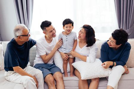 Heureuse famille élargie asiatique assis sur un canapé ensemble, posant pour des photos de groupe