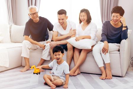 Glückliche asiatische Großfamilie, die zusammen auf Sofa sitzt und kleines Kind beim Spielen Spielzeug auf dem Boden mit Glück beobachtet Standard-Bild