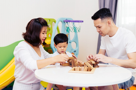 Asian child and parents playing with wooden blocks in the room at home. A kind of educational toys for preschool and kindergarten kids