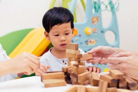 Asian child playing with wooden blocks in the room at home. A kind of educational toys for preschool and kindergarten kids 스톡 콘텐츠