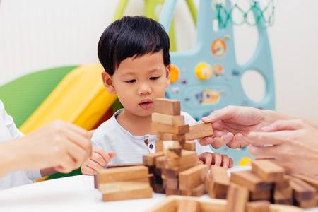 Enfant asiatique jouant avec des blocs de bois dans la pièce à la maison. Une sorte de jouets éducatifs pour les enfants d'âge préscolaire et de maternelle Banque d'images - 100987279