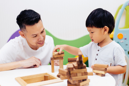 Asian child and father playing with wooden blocks in the room at home. A kind of educational toys for preschool and kindergarten kids Stock Photo