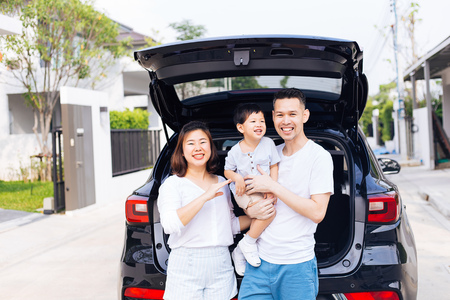 Happy Asian family standing on the back of SUV car with smile and happiness