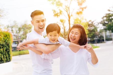 Famille asiatique s'amusant et portant un enfant dans un parc public
