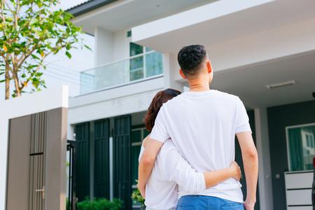 Famiglia asiatica in piedi fuori con la loro nuova casa e scatole di trasporto auto