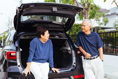 Happy Asian senior couple standing on the back of SUV car, looking at each other with smile and happiness
