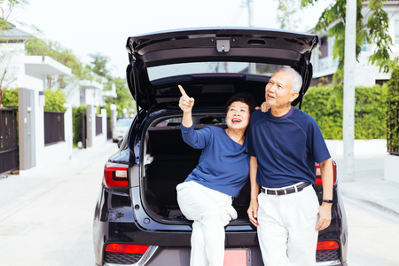 Happy Asian senior couple standing on the back of SUV car, pointing up in the sky with smile and happiness Stock Photo