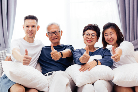 Asiatische Familie mit erwachsenen Kindern und älteren Eltern, die Daumen hoch geben und gemeinsam auf einem Sofa zu Hause entspannen. Glückliche Familienzeit zusammen