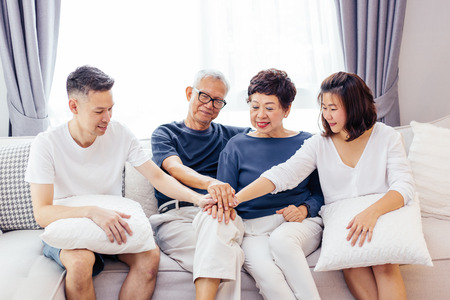 Asian family with adult children and senior parents putting hands together and sitting on sofa at home together. Family unity and cooperation concept