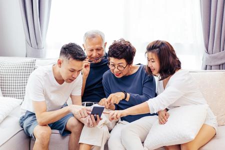 Aziatische gezin met volwassen kinderen en senior ouders met behulp van een mobiele telefoon en samen ontspannen op een bank thuis