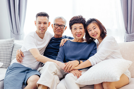 Asian family with adult children and senior parents relaxing on a sofa at home together Stockfoto
