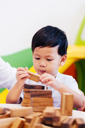 Asian child playing with wooden blocks in the room at home. A kind of educational toys for preschool and kindergarten kids Stock Photo