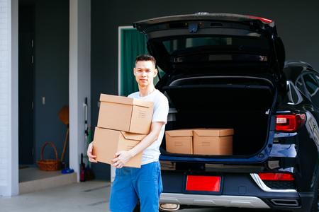Rijpe Aziatische man met kartonnen dozen uit de kofferbak van de auto in het nieuwe huis