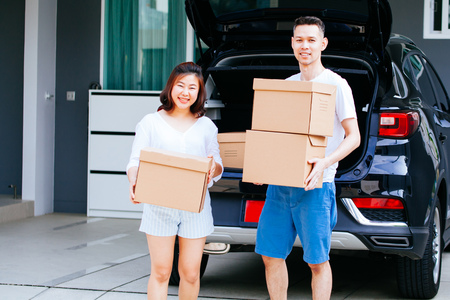 Mature happy Asian married couple carrying cardboard boxes from car trunk at new home