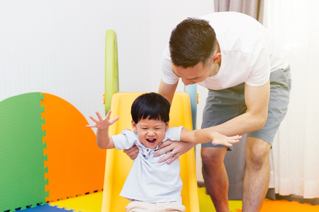 Asian father accompanying child on the playground slider at home. Happy family with toys
