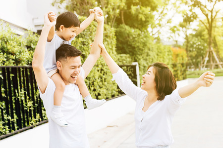 Cute Asian father piggybacking his son along with his wife in the park. Excited family raising hands together with happiness