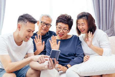 Familia asiática con hijos adultos y padres mayores haciendo una videollamada y saludando a la persona que llama
