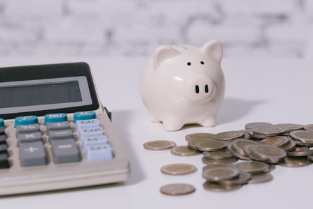Money piggy bank with pile of cash coins and calculator - indicates money savings, banking, investment, depositing, accounting concept