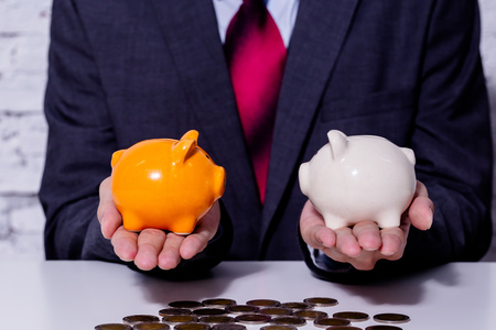 Businessman making a comparison and difference between each money piggy bank - finance issue comparison concept
