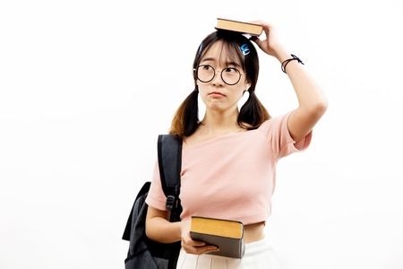 Young Asian female academic teen students with trendy eye glasses holding pile of books with bag isolated over white background 写真素材