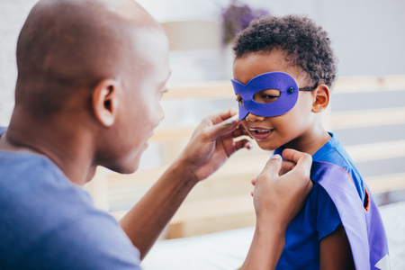 Happy smiling African American son being supported and helped by supportive father for little adventure and protection Stock Photo - 103816409