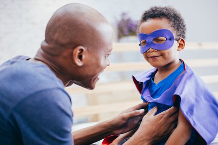 Happy smiling African American son being supported and helped by supportive father for little adventure and protection Stock Photo - 103816411