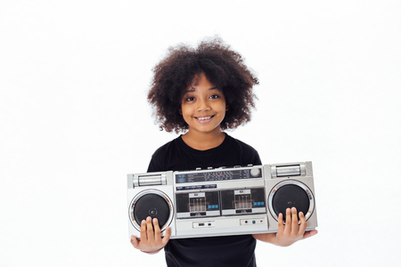 Cute and smiling African American kid holding a musical jukebox isolated over white background Stock Photo