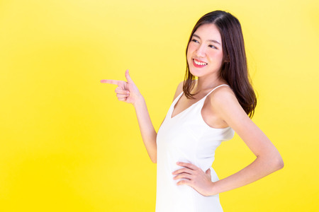 Asian cute woman pointing hands to  empty copy space and posing arms akimbo isolated on yellow background Imagens